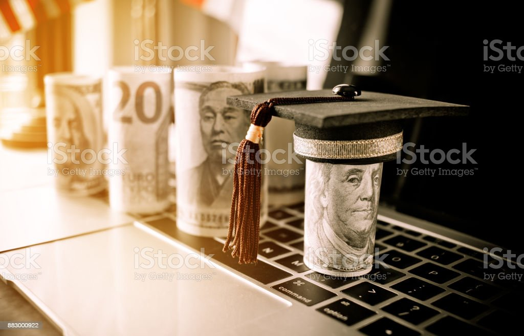 Concept of international graduate study, graduation black cap on pile of foreign money US dollars, Asian, JPY, EURO money on laptop keyboard. Education certificate of Abroad program. Vintage stlye stock photo