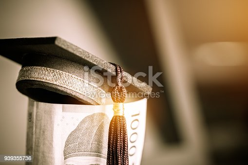 istock Concept of international graduate study, graduation black cap on pile of foreign money KRW bill money on blur background. Education certificate of Korea Abroad program to success. Vintage stlye 939355736