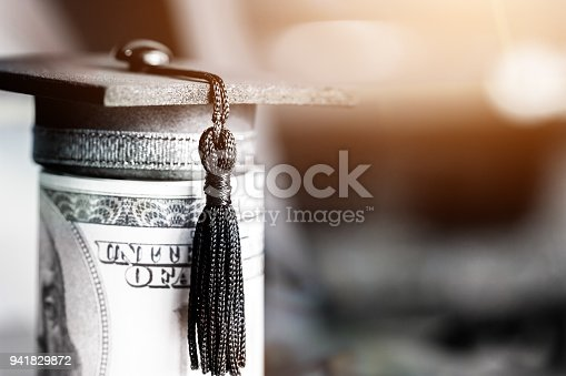 istock Concept of international graduate study, graduation black cap on pile of foreign money US dollars money on blur background. Education certificate of Abroad program to success. Vintage stlye 941829872