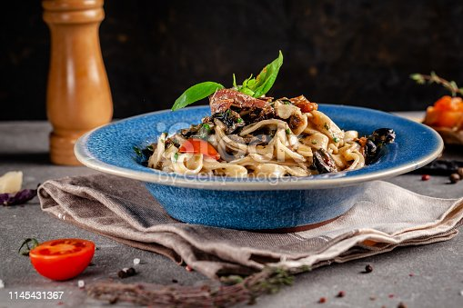 istock Concept of Italian cuisine. Pasta with anchovies, seafood and vegetables, olives, tomatoes and basil. Serving dishes in a restaurant in a blue plate. Background image. copy space 1145431367