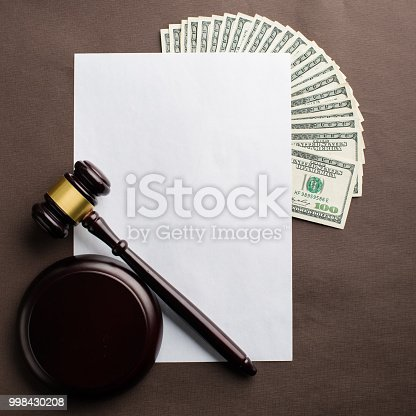 Concept of justice, law and bribery. Sheet of paper with copyspace, money and judges gavel on the table. Top view, flat lay