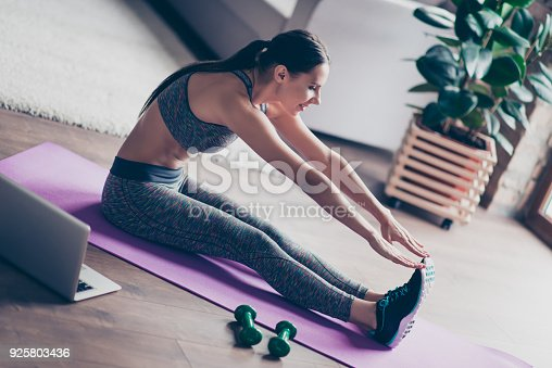 925799546 istock photo Concept of keeping fit leading healthy lifestyle. Pretty charming sexy young woman stretching and warming up her muscles before doing exercises at home in front of laptop 925803436