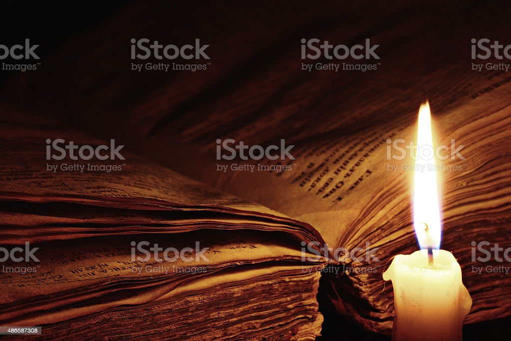 concept of knowledge, vintage book candle stock photo