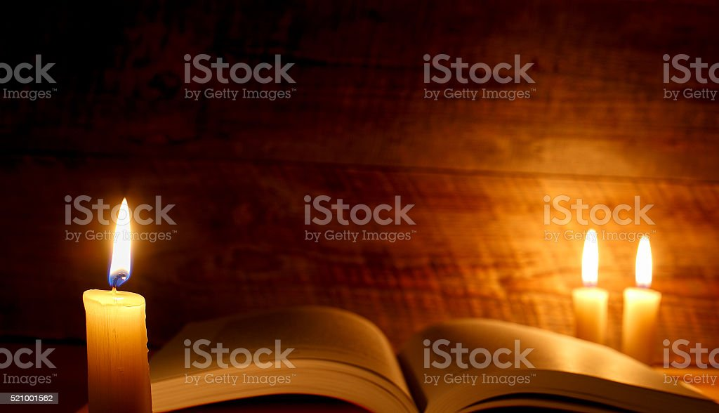 concept of knowledge, vintage book with candle stock photo