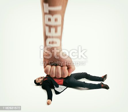 The big human fist with text - debt bring down the man off his feet. Concept of  large debts. Image.