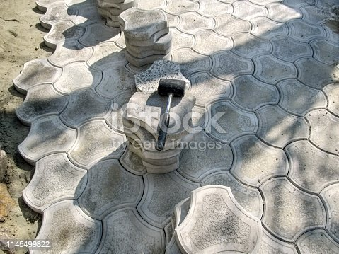 istock Concept of laying decorative paving tiles with a mallet 1145499822