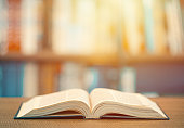 istock Concept of learning education. Open book on the wooden table in the library 1268151176