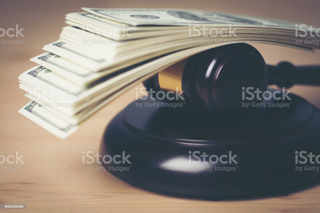 Concept of Legal court gavel on assorted cash, Close up. stock photo