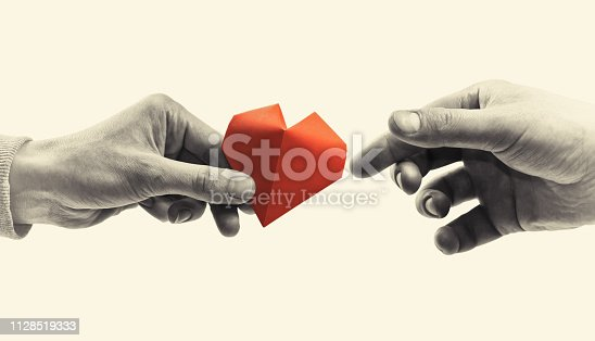 Red heart in woman and man hands. Black and white image. Concept of love,  giving gifts, donorship.