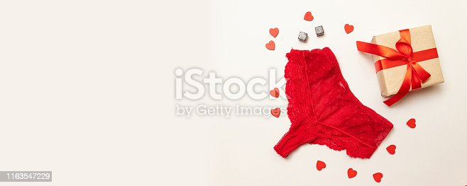 Romantic holiday composition of red lace panties with a surprise gift box wrapped in craft paper and with a red satin ribbon on a pink background. Congratulations on Valentines Day or birthday