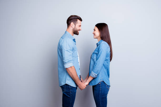 Concept of love. Two young happy people with beaming smile standing face-to-face and holding hands Concept of love. Two young happy people with beaming smile standing face-to-face and holding hands face to face stock pictures, royalty-free photos & images