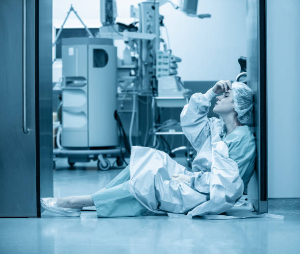 Concept of medecine surgery, Kovid 19. Tired, exhausted doctor after an exhausting shift in the intensive care unit. Pandemic, isolation, epidemic hard work of doctors, stay home. Blue monochrome color stock photo