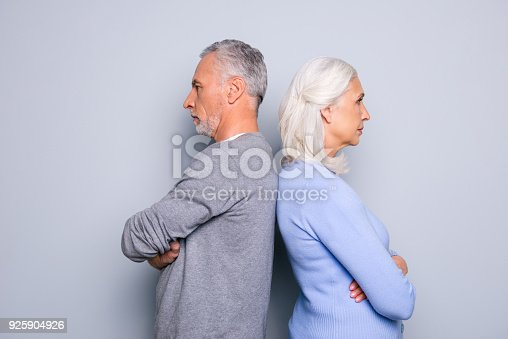 istock Concept of misunderstanding and  communicative problem between two senior people, they are standing back to back, isolated on grey background 925904926