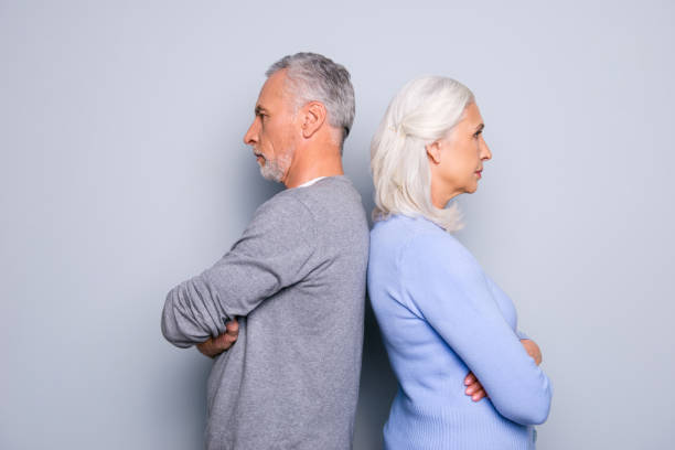 concept of misunderstanding and  communicative problem between two senior people, they are standing back to back, isolated on grey background - gray divorce stock pictures, royalty-free photos & images