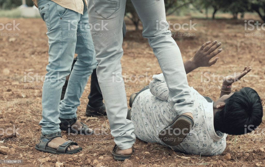 Concept of mob lynching - Group of people bullying, kicking a man - Close up of young adult males hitting a person on ground Concept of mob lynching - Group of people bullying, kicking a man - Close up of young adult males hitting a person on ground. 20-29 Years Stock Photo