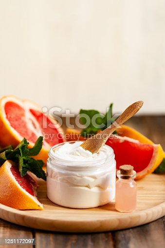 Concept of natural fruity organic ingredients in cosmetology. Extract of grapefruit for moisturizing, delicate skin nutrition, pore narrowing and anti-cellulite effect. Wooden background, copy space