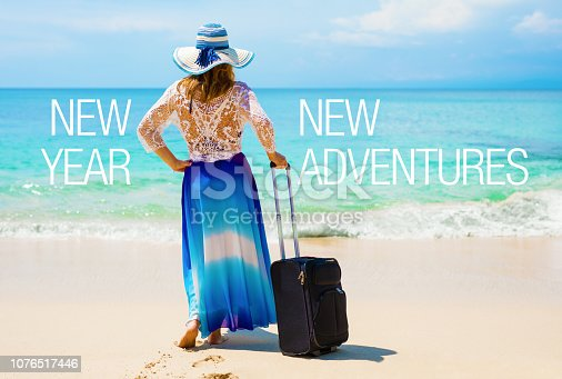 Unrecognizable woman standing in tropical beach with suitcase. Concept of new adventures in New Year