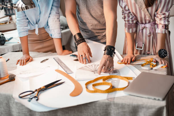 Concept of new design. Drawing new project layout, cropped photo Concept of new design. Close-up group of designers are thinking about new dress. Tailor items are at the table. Scissors, measure tape, ruller, strings fashion designer stock pictures, royalty-free photos & images