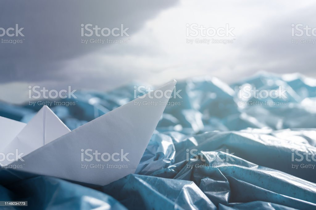 Concept of ocean pollution with plastic. Paper boats in stormy sea...