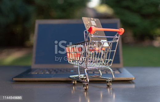 Concept of online grocery shopping. A miniature shopping cart with a credit card is standing an a Notebook.