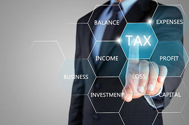 Concept of online taxation on touch screen Mid section view of a businessman hand touching tax word on virtual screen the concept of online taxation. corporate tax stock pictures, royalty-free photos & images