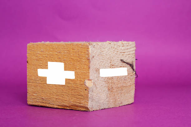 concept of opposites, big wood block with plus and minus on purple background concept of opposites, big wood block with plus and minus on purple background minus sign stock pictures, royalty-free photos & images