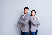 Concept of partnership in business. Young man and woman standing back-to-back with crossed hands against gray background
