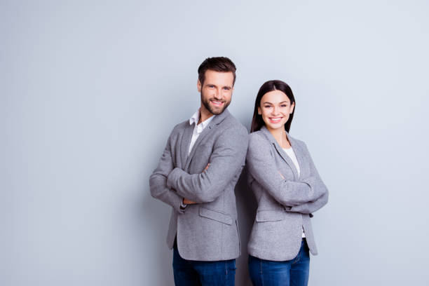 concept of partnership in business. young man and woman standing back-to-back with crossed hands against gray background - woman suit stock photos and pictures