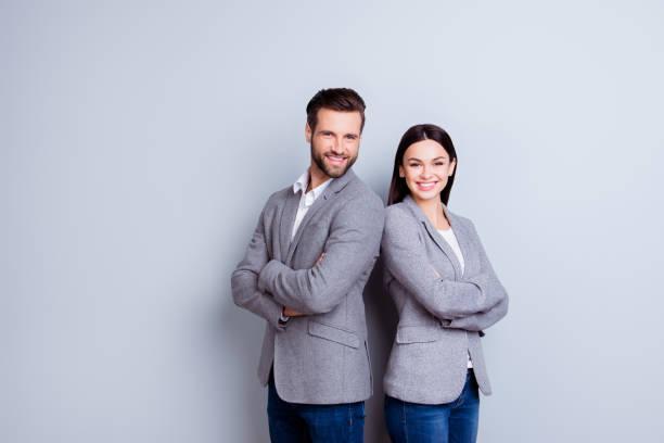 concept van partnerschap in het bedrijfsleven. jonge man en vrouw permanent back-to-back met gekruiste handen tegen de grijze achtergrond - man woman stockfoto's en -beelden