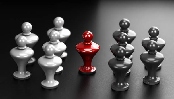 Concept of pawns representing conflict between groups and one mediator in the middle. stock photo