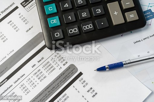 istock Concept of paying bills. Close up cropped photo with flat lay high angle above top view of object blank calculator and pen 1078060350