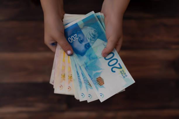 konzept der zahlung geld, zwei kinderhände holding israelischen banknoten in 200 schekel ils - kindergeldantrag stock-fotos und bilder