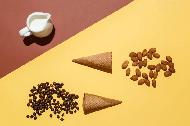 konzept der vorbereitung auf eis oder eiskaffee. sahnekännchen, zwei waffel-cups, verstreuten kaffeebohnen und mandeln auf gelb braunen tisch. flache laien mockup - hausgemachter eiskaffee stock-fotos und bilder