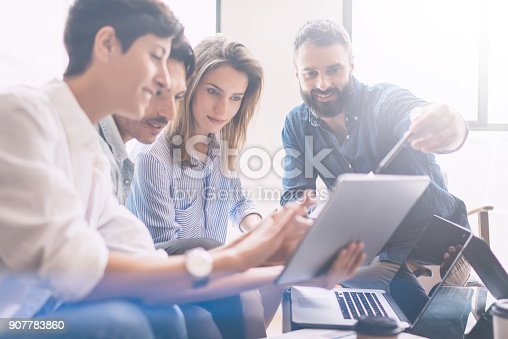 istock Concept of presentation new business project.Group of young coworkers discussing ideas with each other in modern office.Business people using electronic devices.Horizontal, blurred background. 907783860