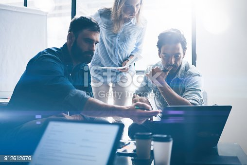 istock Concept of presentation new business project.Group of young coworkers discussing ideas with each other in modern office.Business people using electronic devices.Horizontal, blurred background. 912612676