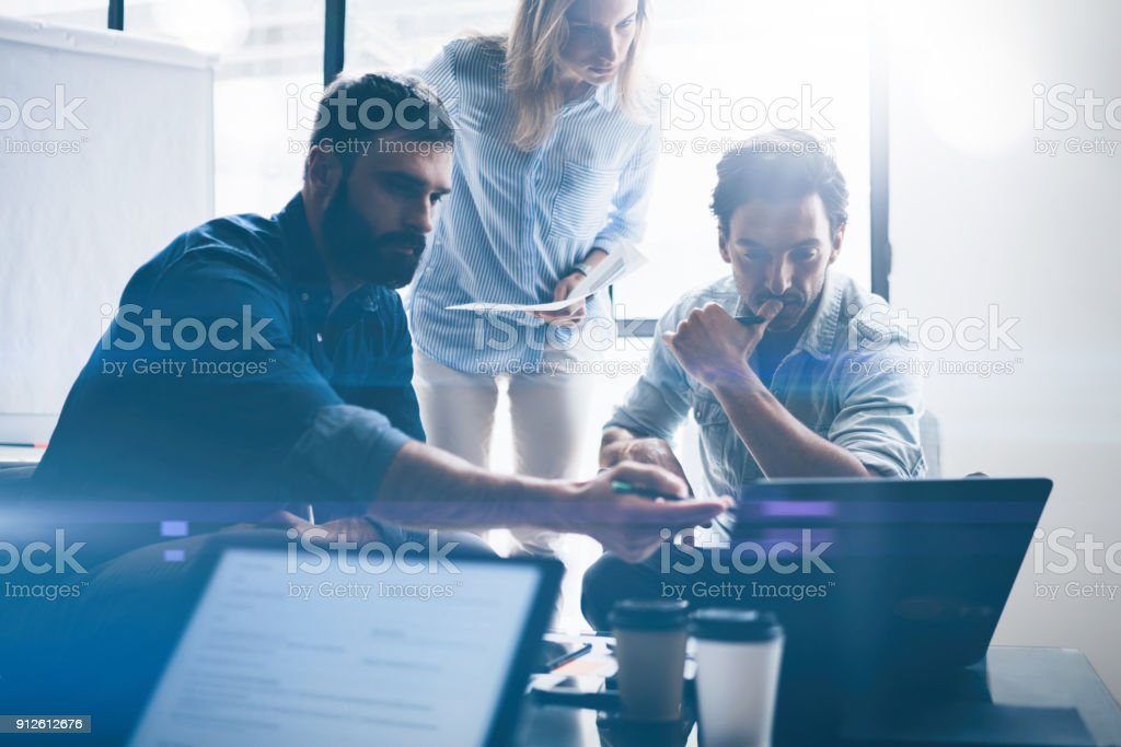 Concept of presentation new business project.Group of young coworkers discussing ideas with each other in modern office.Business people using electronic devices.Horizontal, blurred background. stock photo
