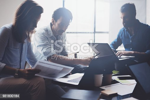 istock Concept of presentation new business project.Group of young coworkers discussing ideas with each other in modern office.Business people using electronic devices.Horizontal, blurred background. 931830184