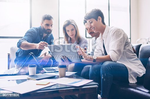 istock Concept of presentation new startup project.Group of young coworkers discussing ideas with each other in modern office.Business people using electronic devices.Horizontal, blurred background. 907781604