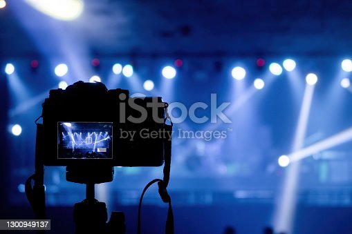 Concept of production in pubs and concert events, camera shooting beams from spotlights and lights in blue tones.
