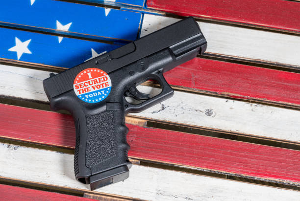 Concept of protecting against voter fraud with firearm and voting sticker stock photo