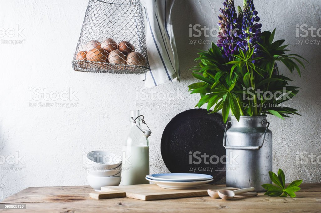 Concept of rural kitchen. Lupines in a can, milk, eggs and ware on a wooden table against the background of a white wall stock photo