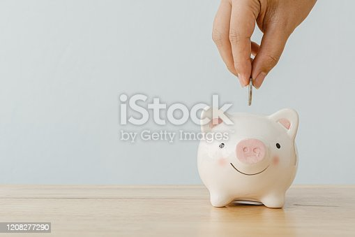 929887844 istock photo Concept of save money financial business investment. Hand of a man putting coins in piggy bank on wood table 1208277290