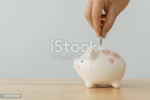 929887844 istock photo Concept of save money financial business investment. Hand of a man putting coins in piggy bank on wood table 1227259161
