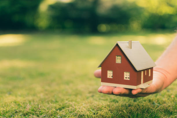 Concept of selling a house. A hand is holding a model house above green meadow. stock photo