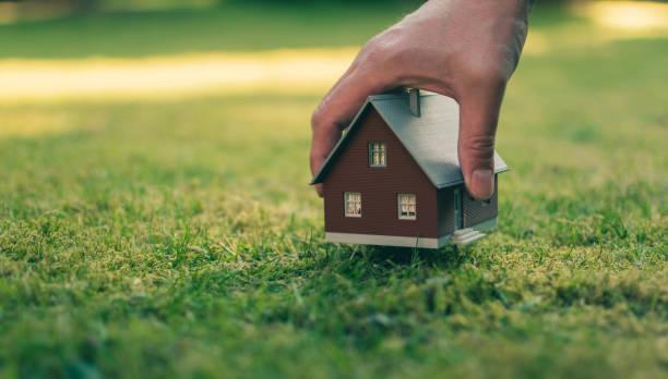 concetto di vendita di una casa. una mano tiene una casa modello sopra il prato verde. - costruire foto e immagini stock