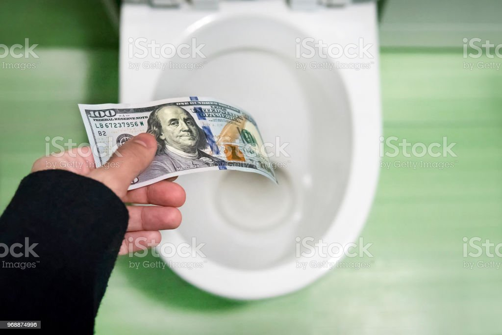concept of senseless waste of money, loss, useless waste, large water costs, 100 Dollar bills flushed into a toilet bowl concept of senseless waste of money, loss, useless waste, large water costs, 100 Dollar bills flushed into a toilet bowl. loss of money, losing money Bailout Stock Photo