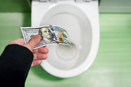 Concept Of Senseless Waste Of Money Loss Useless Waste Large Water Costs 100 Dollar Bills Flushed Into A Toilet Bowl Stock Photo - Download Image Now