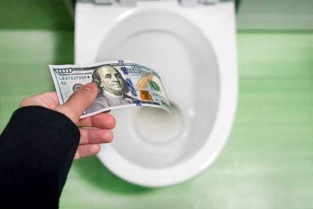 concept of senseless waste of money, loss, useless waste, large water costs, 100 dollar bills flushed into a toilet bowl - throw money away stock pictures, royalty-free photos & images