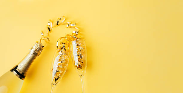 Concept of serving champagne on a yellow background stock photo