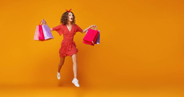 concept of shopping purchases and sales of happy   girl with packages  on yellow background - jumping zdjęcia i obrazy z banku zdjęć